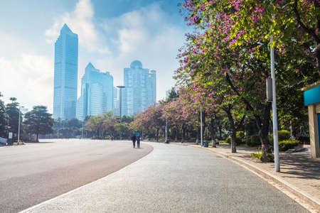 escena de la calle de Guangzhou, la carretera de asfalto con modernos edificios y árboles Bauhinia, China