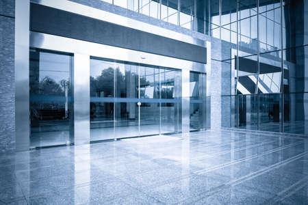 近代的なオフィスビル ゲート入り口と青色のトーンで自動のガラス扉