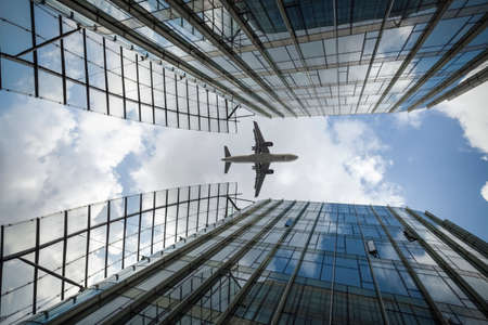 flew: airliner flew above the modern glass building Editorial