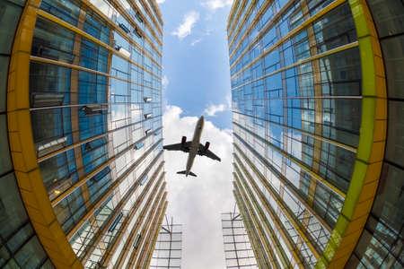 flew: airplane flew above the modern glass buildings, fisheye view