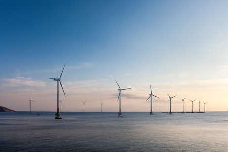 夕暮れ、再生可能エネルギーの背景で洋上風力発電ファーム