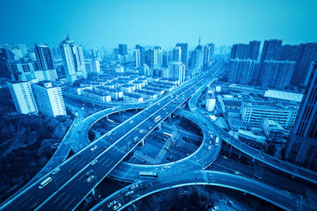 light circular: city overpass in shanghai with blue tone, circular flyover and traffic light intersection