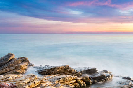 horizon over water: beautiful seascape of reef with sunset glow over the sea