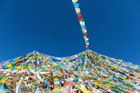 the wind-horse flags on tibetan snow mountain,the symbol of harmony among heaven,earth,human beings and animals. Stock Photo