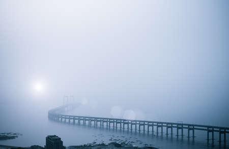heavy: bay bridge in heavy fog with morning sun, dalian, China