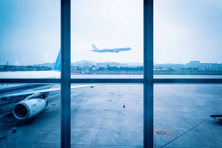 airport window scene, a departing flight, blue tone