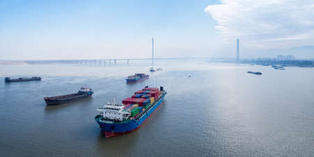 container ships waiting to enter port at anchor on yangtze river with jiujiang cable-stayed bridge , water transport concept Standard-Bild