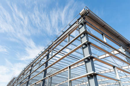 steel frame workshop is under construction against a blue sky