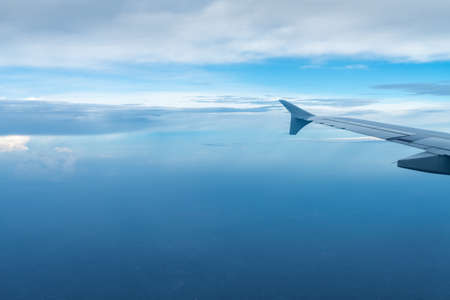 plane wing view in the sky, taking an airplane trip Stock Photo