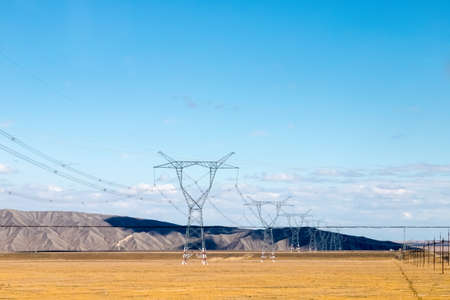 Transmission towers in the prairie under the blue sky