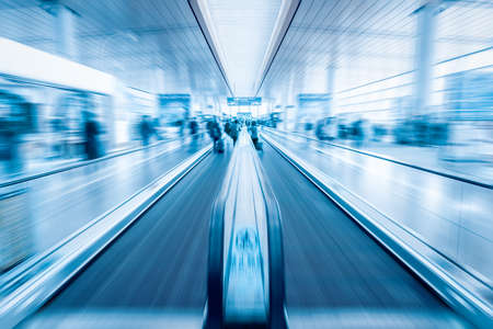 modern passenger conveyor motion blur in airport terminal with blue tone