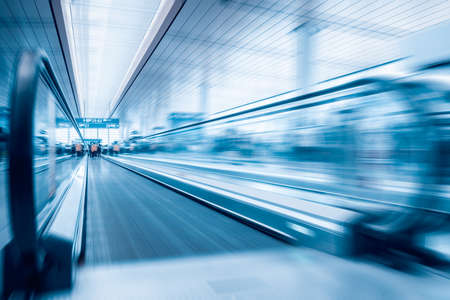 modern passenger conveyor motion blur in airport hall