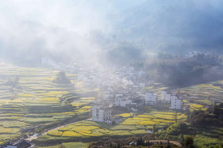 beautiful wuyuan mountain village in morning mist, rapeseed flowers blooming in Chinas most beautiful countryside.