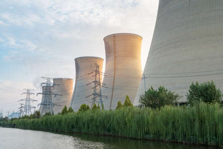 power plant at dusk, sunset light shines on the cooling towers Archivio Fotografico