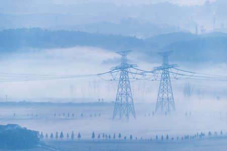 electric towers in the morning fog,  beautiful natural scenery and ultra-high voltage power transmission background Imagens
