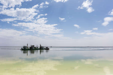salt mining ship and blue sky reflection in qarhan salt lake, golmud city, qinghai province, China