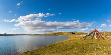 beautiful plateau sacred lake and bright flapping prayer flags, stars sea at madoi county, qinghai province, China