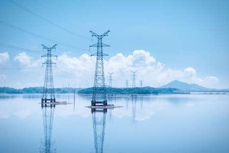 power transmission pylon on lake and reflection