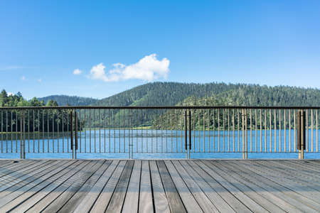 beautiful lake scene and wooden floor with railing against a pure sky in alpine forest park