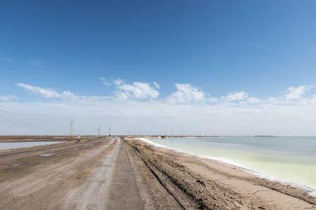 Dirt road on salt lake against blue sky