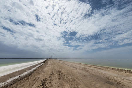salt lake and dirt road against cloudy sky, qinghai province, China