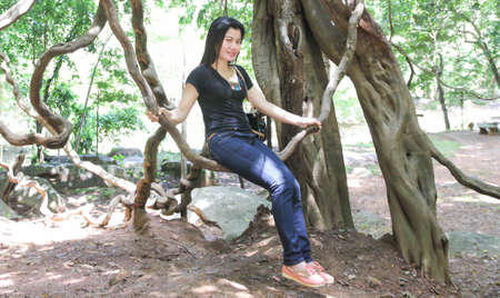 under a tree: A woman sitting under a tree.