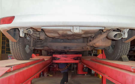 repaired: The car was repaired on a lift in the garage.