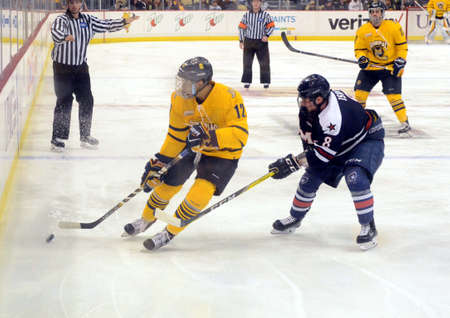 Robert Morris University defender Eric Israel pressures Quinnipac University forward Thomas Aldworth along the boards.