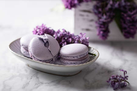 macaroons with lilac flowers on a marble background, horizontal orientation