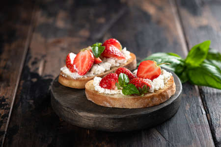 Two bruschettas with strawberries, cream cheese and basil on a round wooden board on an old wooden background