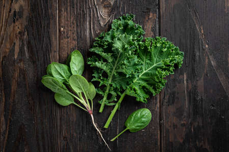 kale and spinach on a dark wooden background