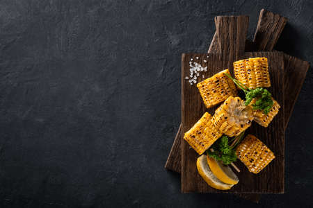 grilled corn on cob on a dark background, top view, copy space