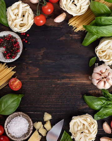 italian food ingredients background. Spaghetti, tagliatelle pasta, basil, parmesan, tomatoes, garlic on an old rustic wooden table, top view, place for text