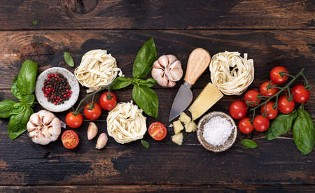 italian food ingredients background. Spaghetti, tagliatelle pasta, basil, parmesan, tomatoes, garlic on an old rustic wooden table, top view Reklamní fotografie - 154076889