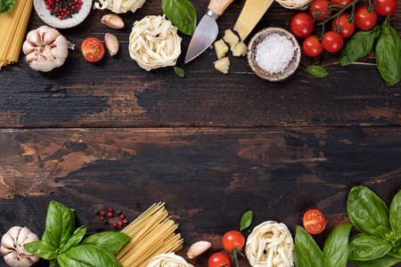 italian food ingredients background. Spaghetti, tagliatelle pasta, basil, parmesan, tomatoes, garlic on an old rustic wooden table, top view Reklamní fotografie