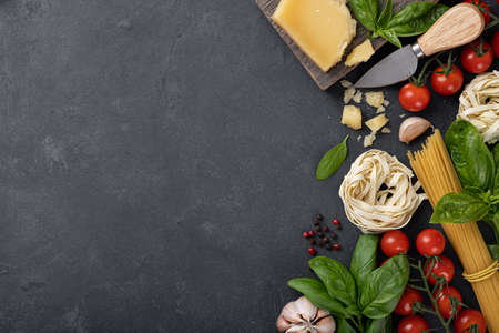 Italian food ingredients background. Spaghetti, tagliatelle pasta, basil, parmesan, tomatoes, garlic on a dark stone table, top view, place for text