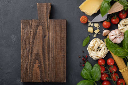 Italian food ingredients background. Spaghetti, tagliatelle pasta, basil, parmesan, tomatoes, garlic on a dark stone table, top view, place for text Reklamní fotografie - 154076898