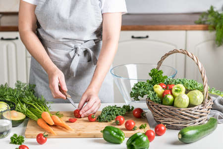 woman cooking in the kitchen. fresh healthy vegetables on a cutting board Reklamní fotografie - 154076925