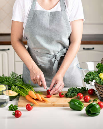 woman cooking in the kitchen. fresh healthy vegetables on a cutting board Reklamní fotografie - 154076942