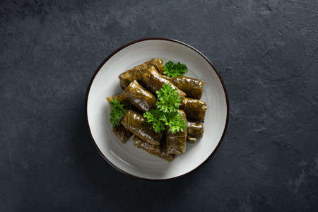 Dolma - stuffed grape leaves with rice and meat on a dark background, view from above, copy space. Traditional Greek. Caucasian and Turkish cuisine Reklamní fotografie