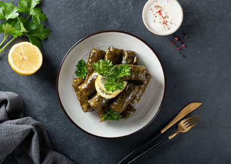 Dolma - stuffed grape leaves with rice and meat on a dark background, view from above. Traditional Greek. Caucasian and Turkish cuisine Reklamní fotografie - 154077011