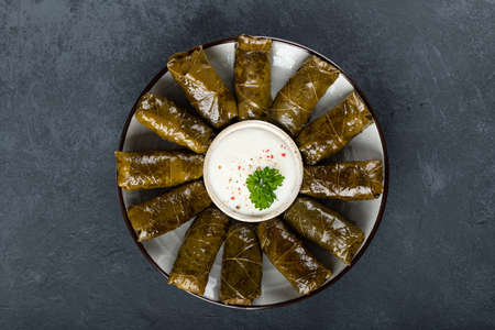 Dolma - stuffed grape leaves with rice and meat on a dark background, view from above. Traditional Greek. Caucasian and Turkish cuisine Reklamní fotografie - 154077029