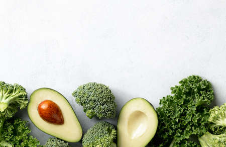 Avocado, kale and broccoli, detox dieting concept. Green vegetables on a white background, top view, border