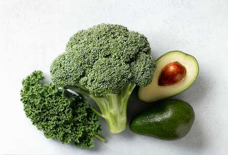 Avocado, kale and broccoli, detox dieting concept. Green vegetables background, top view Reklamní fotografie