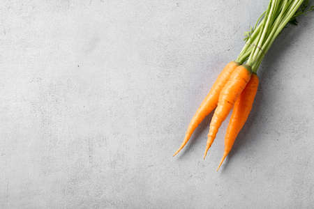 organic carrots with tops on light background, top view, copy space Reklamní fotografie