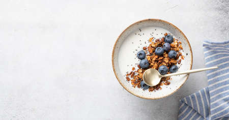 Breakfast, granola with yogurt, blueberries, chia seeds, pumpkin seeds on a light background, top view, copy space Reklamní fotografie