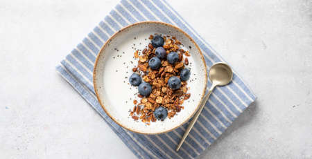 Breakfast, granola with yogurt, blueberries, chia seeds, pumpkin seeds on a light background, view from above Reklamní fotografie - 153737215