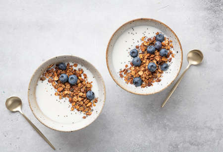 Breakfast, granola with yogurt, blueberries, chia seeds, pumpkin seeds on a light background, view from above