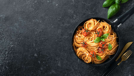 pasta in a black pan on a dark background , italian cuisine. Top view, copy space Reklamní fotografie - 153737221