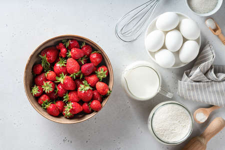 Ingredients for cooking strawberry pie on white background, top view. Strawberry, eggs, flour, milk, sugar.